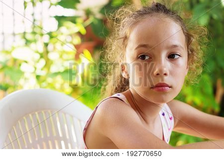 Sad Beautiful little girl is looking with serious face in the summer Garden.