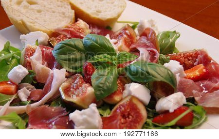 Mediterranean salad with fig prosciutto ham rucola and basil leaf