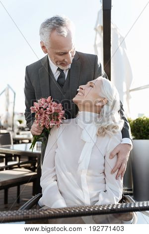 I am here. Handsome bearded man bowing his head to his sweetheart, holding flowers in right hand while embracing her with left one
