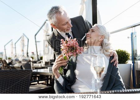Like a fairy tale. Delighted female turning her head while smiling to her boyfriend and taking nice flowers