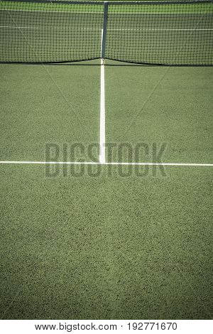 Centre of all weather tennis court in bright sunshine