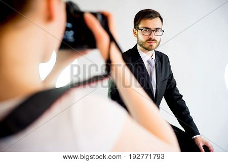 Photographer girl photographing a model of a man on a white background in a photo studio