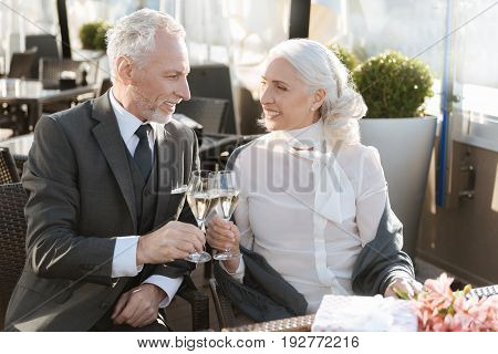 It is our secret. Confident gentleman turning head to his partner and expressing positivity while touching glasses