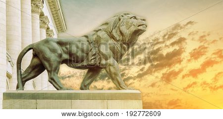 Big ancient archeology statue of lion with burning sun