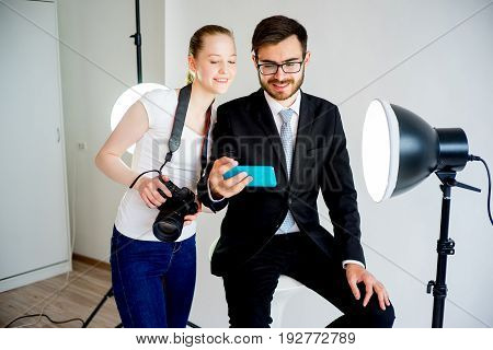 Photographer and model taking selfie in a studio