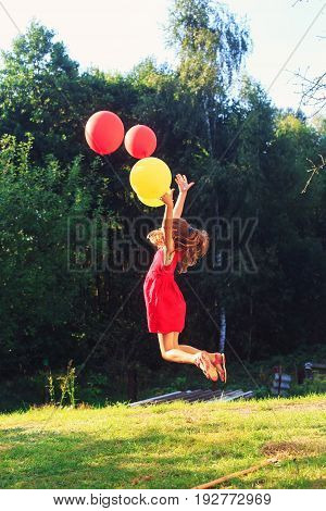 Happy child jumping with colorful toy balloons outdoors. Smiling kid having fun in green spring garden against at warm summer day. Freedom concept