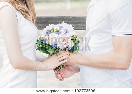 hands of the bride and groom hold a beautiful wedding bouquet