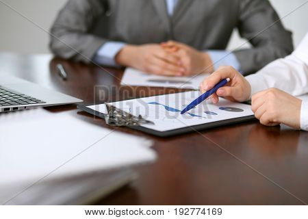 Close up of unknown business people at meeting discussing financial results.