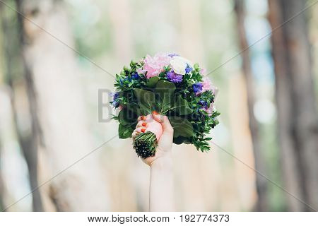 bridesmaid caught a wedding bouquet.  female hand holds a bouquet at the top