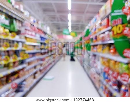 Abstract blurred supermarket aisle with colorful shelves and unrecognizable customers as background in Thailand