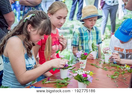 Zaporizhia/Ukraine- May 28, 2017: Charity Family festival:  teen girls participating at outdoors floristic workshop, learning to arrange fresh flowers into beautiful bouquets