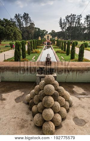 Mysore India - October 26 2013: Grounds and green and red park of Tipu Sultan Summer Palace named Daria Daulat Bagh. Entry gate to park at end of visual lines. Cannon and balls in front. View from palace.