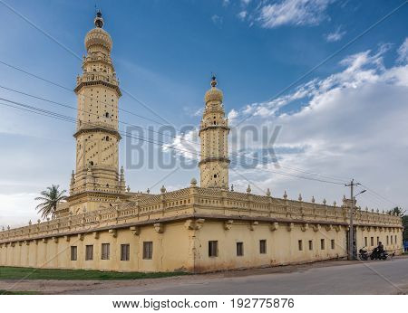Mysore India - October 26 2013: Grounds walls mosque and minarets of Jamia Masjid mosque on Sriranagapatna Island under blue cloudy sky. Cream yellow building.