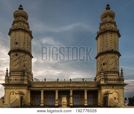 Mysore India - October 26 2013: Upper structure with two minarets of Jamia Masjid mosque on Sriranagapatna Island. Doubles as pigeon housing. Rain storm gathers and darkens sky.