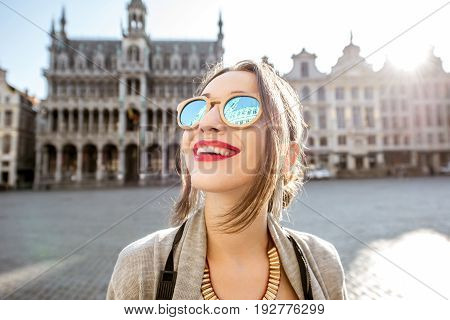 Young excited woman standing on the central square of the old town in Brussels during the morning. City hall reflected on the sunglasses