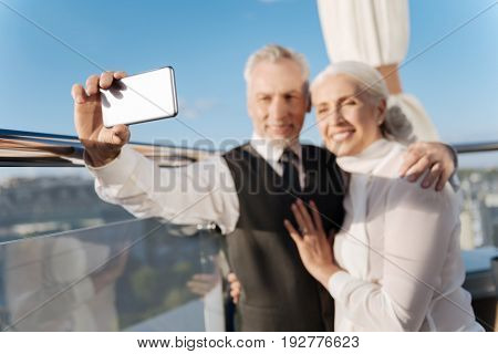 Selfie time. Positive delighted couple of lovers hugging while standing close to each other when mature man keeping phone in right hand