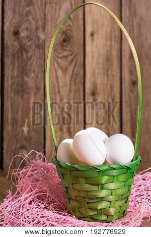 White eggs in the green basket on wooden background with pink napkin