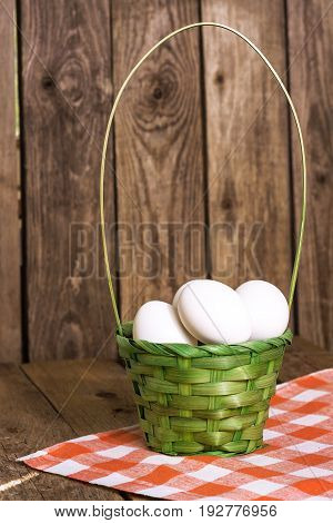 White eggs in the green basket on tablecloth on wooden background