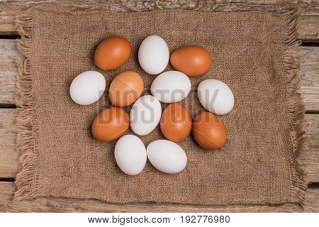Top view of eggs on sackcloth on old wooden table