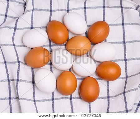 Top view of eggs on checkered kitchen towel