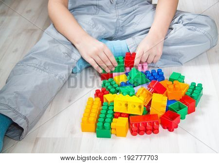 Toddler baby builds a house from a designer close-up lifestyle in a real interior light background toning