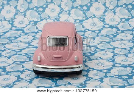 XALAPA, VERACRUZ, MEXICO- APRIL 19, 2017: Pink toy Volkswagen Super Beetle car on a flowers background.