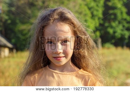 Beauty Girl Outdoors enjoying nature. Beautiful Teenage girl with long hair dreaming. Serious kid. Toned in warm colors