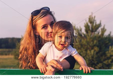 Portrait of mother and little baby girl hugging at sunset