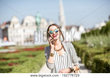 Young woman walking with phone on the famous arts mountain with great view on the old city of Brussels in Belgium