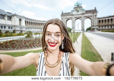 Young female traveler making selfie photo on the famous Triumphal arch background in Brussels