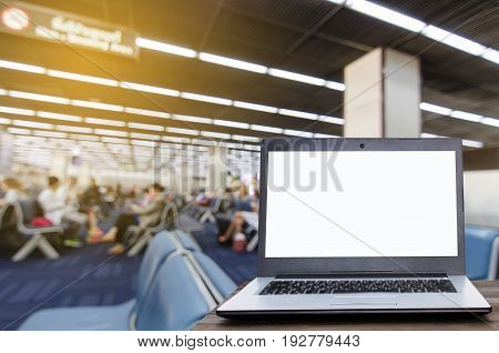 Laptop computer with white blank screen on wooden table with blurred in airport terminal waiting room selective focus copy space working outside office online social media searching data concept