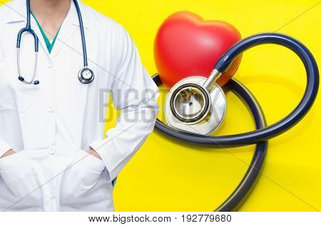 smart doctor with a stethoscope around his neck with red heart and stethoscope on yellow background heart health care and medical technology concept selective focus copy space