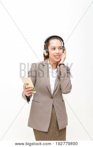 beautiful asian young business woman smiling in suit standing relaxing and using smartphone listening to music in headphone isolated on white background