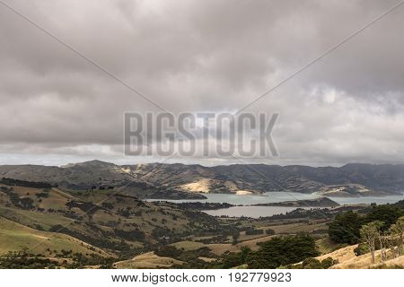 Akaroa New Zealand - March 14 2017: The Akaroa Sound is an inlet from Pacific ocean in the remnants of a Miocene volcano. Heavy cloudscape and from the higher up hills. Vegetation in several shades.