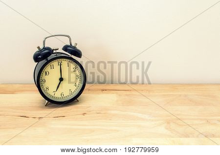 retro black color alarm clock times at 7 o'clock morning on wooden table table and white wall vintage tone