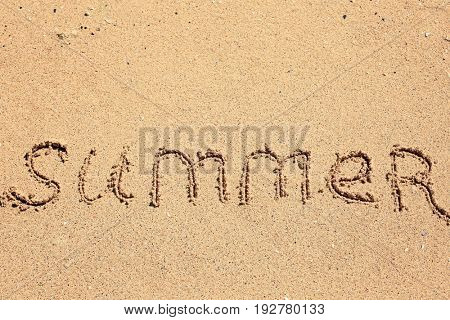 Word SUMMER written on beach sand. Vacation concept