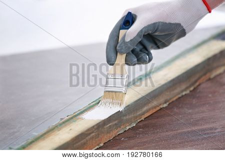 Worker painting frame of old window lying on wooden table, closeup