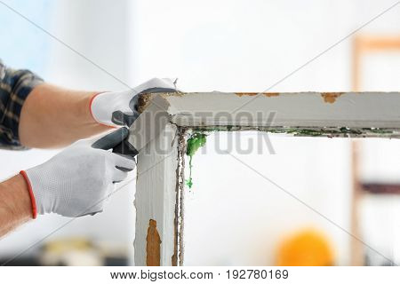 Worker removing paint from old window frame, closeup