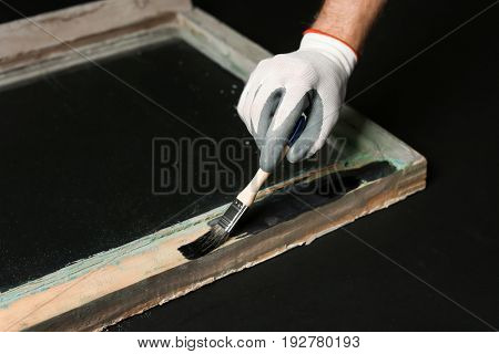 Hand of worker painting frame of old window, on dark background