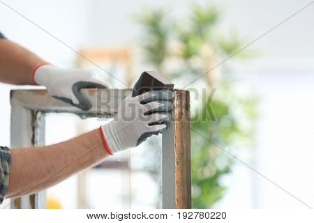 Worker grinding surface of old window frame with abrasive stone, closeup