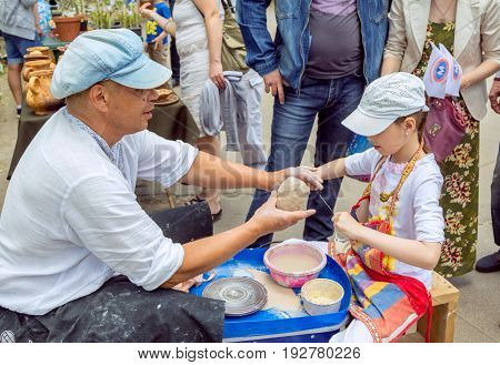Zaporizhia/Ukraine- May 28, 2017: Charity Family festival:  Outdoors pottery workshop - ceramist master helps girl to cut a piece of clay with a string. Art and craft activity.