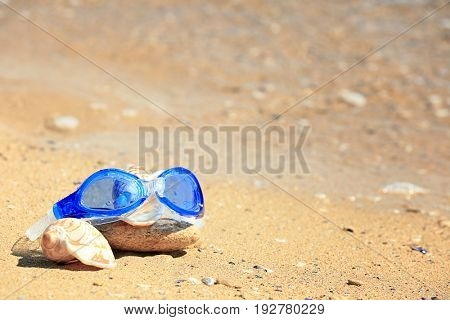 Swimming goggles, shells and stone on sand at sea shore. Vacation concept