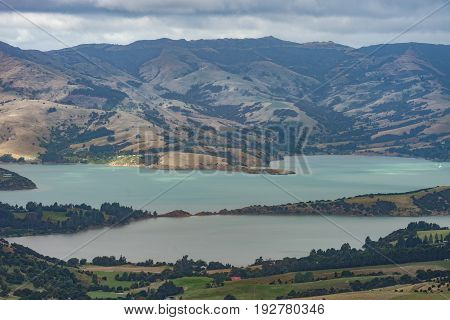 Akaroa New Zealand - March 14 2017: Turquoise Akaroa Sound is inlet from Pacific ocean in remnants of Miocene volcano. Seen under heavy cloudscape and from higher up. Vegetation shades on hills.