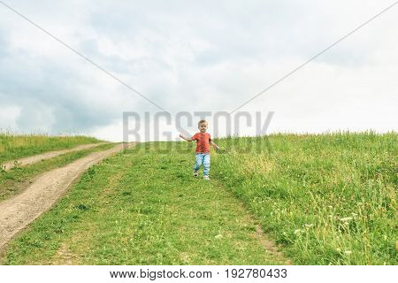 Little boy running across the field on the lawn on a hot summer day