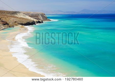 Aerial view on the beach with amazing water colors of the Atlantic Ocean in Mal Nombre on the Canary Island Fuerteventura in Spain closed to Morro Jable and Sotavento beaches.
