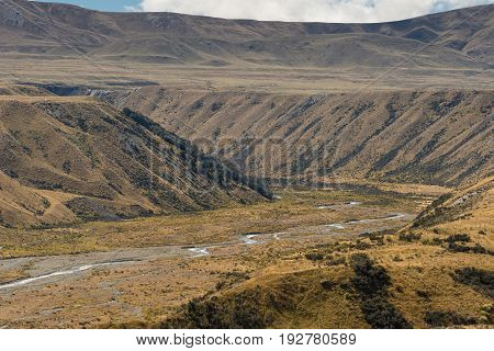 Middle Earth New Zealand - March 14 2017: Closeup High desert landscape with Lake Clearwater meandering shallow overflow drain to Rangitata River. Set in brown dry vegetation on mountains.