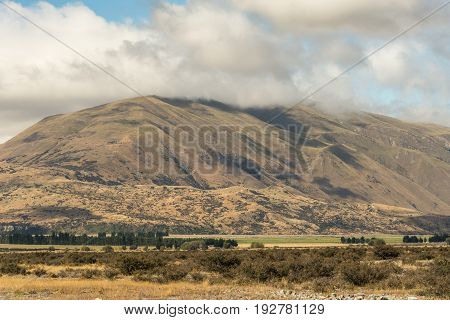 Middle Earth New Zealand - March 14 2017: High mountain with top in clouds at Rock of Middle Earth under blue sky with white clouds. Set in a high desert mountainous scenery.