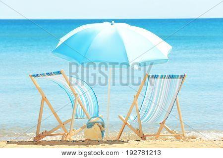 Pair of beach chairs and umbrella at sea shore. Vacation concept