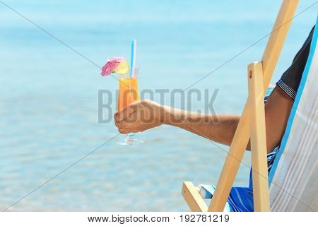 Young man with cocktail sitting on beach chair at sea shore. Vacation concept
