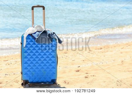Packed suitcase and beach accessories at sea shore. Vacation concept